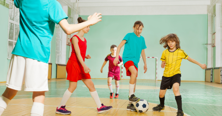 Children playing football in sports hall